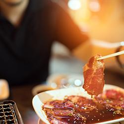 Raw beef or pork slice for charcoal grill, Yakiniku Japanese style barbecue, man using chopsticks, street food concept, depth of field and soft light effect